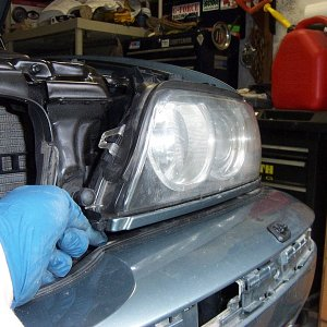 Remove the headlights, or at least loosen enough for bumper to seat under the lights.